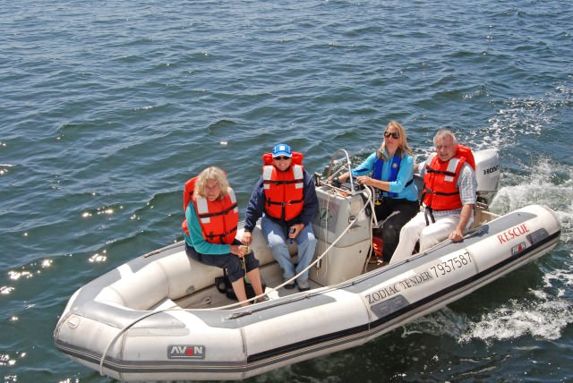 Jacki takes passengers on a tender ride to view Schooner Zodiac while sails are raised.