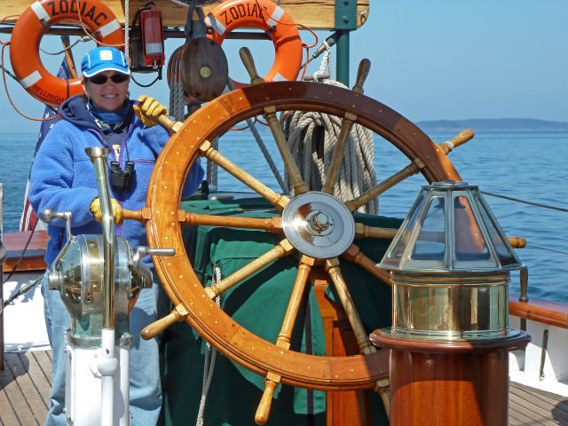 Jill at the helm of Schooner Zodiac while sailing in the San Juan Islands